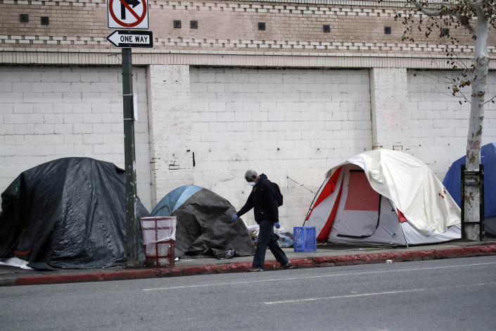 """FILE - In this March 20, 2020 file photo a man covers his face with a mask as he walks past tents on skid row, in Los Angeles. A fed-up federal judge says last week's rainstorm created """"extraordinarily harsh"""" conditions for homeless residents of Los Angeles and he has ordered city officials to meet with him this week at a Skid Row shelter to discuss how to address the worsening crisis of people living on the streets. (AP Photo/Marcio Jose Sanchez,File)"""