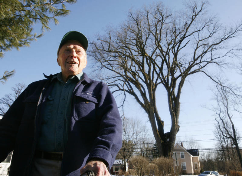 """FILE - In this Dec. 14, 2009 file photo, Frank Knight stands in front of New England's tallest elm tree, known as """"Herbie,"""" in Yarmouth, Maine. Knight, who took care of the tree for five decades while working as the Yarmouth tree warden, died in Scarborough, Maine, Monday, May 14, 2012. He was 103. (AP Photo/Steven Senne, File)"""