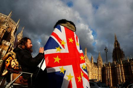 An anti-Brexit demonstrator wears a Union flag decorated with the stars of the EU flag opposite the Houses of Parliament in London