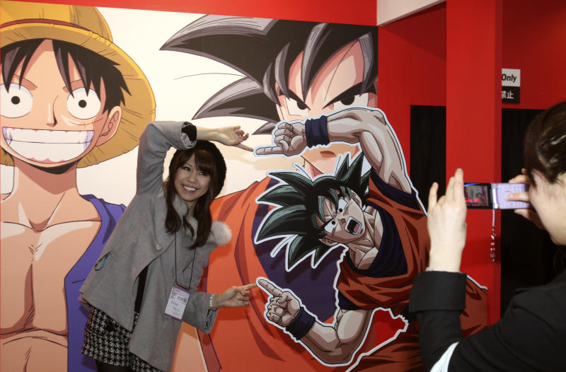 A visitor poses with Son Goku, the main character of Japan's popular manga series Dragon Ball, for a snap during the business day of Tokyo International Anime Fair 2010 in Tokyo, Japan, Thursday, March 25, 2010. More than 200 anime-related companies and organizations gathered in this annual event that opens to public on March 27 and 28. (AP Photo/Koji Sasahara)