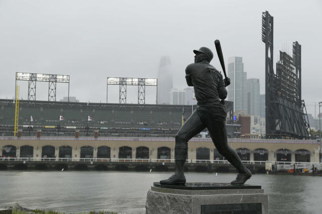 A statue of Hall of Famer Willie McCovey stands in the rain outside Oracle Park before the start of an opening day baseball game between the Tampa Bay Rays and San Francisco Giants Friday, April 5, 2019, in San Francisco. McCovey, who passed away last October, is to be paid tribute during pre-game ceremonies. (AP Photo/Eric Risberg)