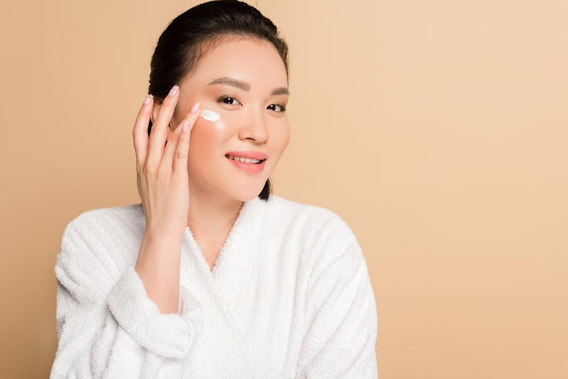 smiling beautiful asian woman in bathrobe applying face cream on beige background