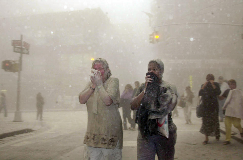 FILE — In this Sept. 11, 2001 file photo, people covered in dust from the collapsed World Trade Center buildings, walk through the area, in New York. Two decades after the twin towers' collapse, people are still coming forward to report illnesses that might be related to the attacks. (AP Photo/Suzanne Plunkett, File)