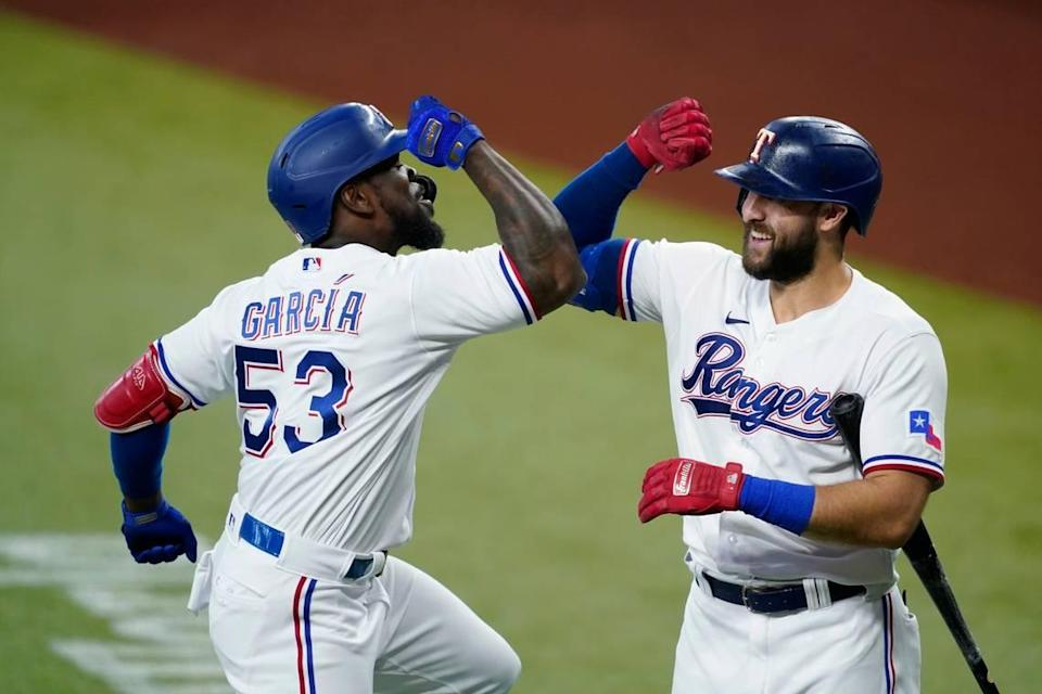 Texas Rangers' Adolis Garcia (53) and Joey Gallo, right, celebrate Garcia's solo home run in the first inning of a baseball game against the Oakland Athletics in Arlington, Texas, Saturday, July 10, 2021. (AP Photo/Tony Gutierrez)