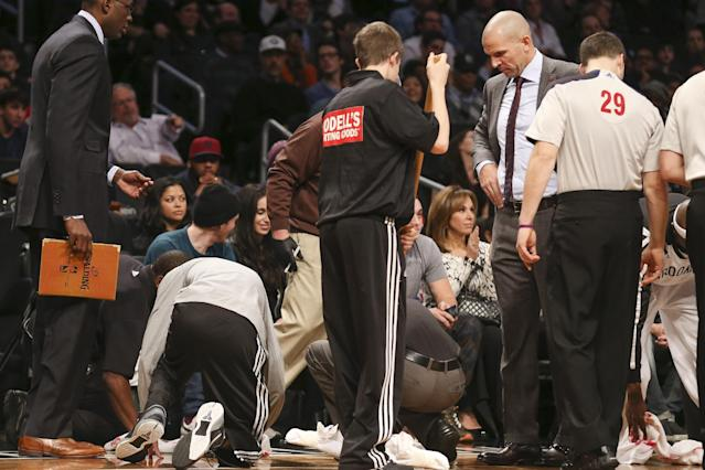 In this photo taken on Wednesday, Nov. 27, 2013, Brooklyn Nets head coach Jason Kidd, center right, watches as attendants clean up a spilled drink beside the Nets bench in the second half of an NBA basketball game at the Barclays Center in New York. The Lakers defeated the Nets 99-94. The NBA fined the Brooklyn Nets coach on Thursday, saying he intentionally spilled his drink on the court as an unusual stall tactic. (AP Photo/John Minchillo)