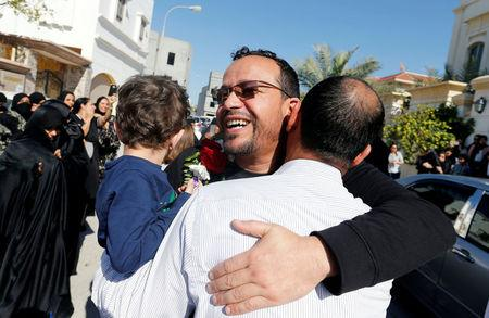 Ali Al-Ekri hugs his family member as he is welcomed home after completing his five-year sentence, in Manama