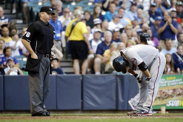 Home plate umpire Mike Muchlinski watches as Minnesota Twins' Kurt Suzuki, right, reacts after striking out during the fourth inning of a baseball game against the Milwaukee Brewers, Monday, June 2, 2014, in Milwaukee. (AP Photo/Morry Gash)