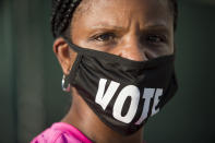 "FILE - In this Oct. 26, 2020, file photo, Caprice Clipps wears a ""vote"" mask as she waits outside the Smoothie King Center in New Orleans for one of the last days of early voting. Several years since its founding, BLM has evolved well beyond the initial aspirations of its early supporters. Now, its influence faces a test, as voters in the Tuesday, Nov. 3 general election choose or reject candidates who endorsed or denounced the BLM movement amid a national reckoning on race. (Chris Granger/The Advocate via AP, File)"