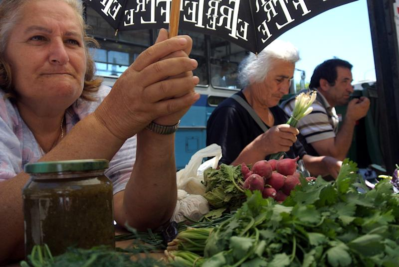 A  street vendor holds an umbrella to avoid the sun in the northern port city of Thessaloniki, Greece, on Tuesday, June 19, 2012. European leaders are locked in a fierce debate over how to solve the debt crisis that is killing off growth on the continent, including whether to ease up on the terms of Greece's bailout deal.(AP Photo/Nikolas Giakoumidis )