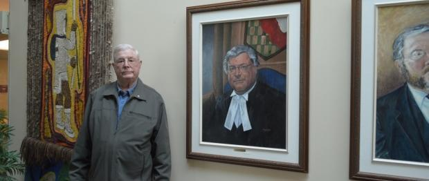 David Searle, seen here in the N.W.T. Legislature in July 2018, standing beside his Speakers portrait. (Submitted by Katie Weaver - image credit)
