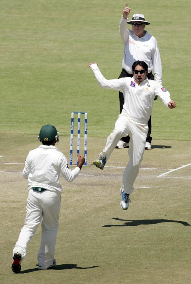 Pakistan's bowler Saeed Ajmal (C) celebrates a wicket on the fifth day of the first test match between Pakistan and Zimbabwe at the Harare Sports Club on September 7, 2013. AFP PHOTO / JEKESAI NJIKIZANA        (Photo credit should read JEKESAI NJIKIZANA/AFP/Getty Images)