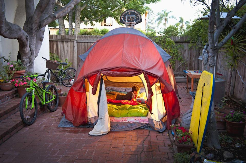 """<p>If you have the room, this is a great way to """"get out"""" this summer, without going too far. Share scary stores, make some s'mores, and doze off under the stars. """"One classic idea you can't go wrong with is the backyard camp-out,"""" says Theresa Bertuzzi, co-owner and co-founder of Tiny Hoppers. """"Get some blankets, pillows, and sleeping bags ready, because it's time to turn your backyard into a weekend adventure. Kids love to make a pretend campfire and roast marshmallows, play board games and just spend time being lazy in the tent."""" If you're a city dweller, or prefer not to camp outside, bring the tent indoors. Use some imagination and turn any room in your house into an outdoor oasis.<br></p>"""