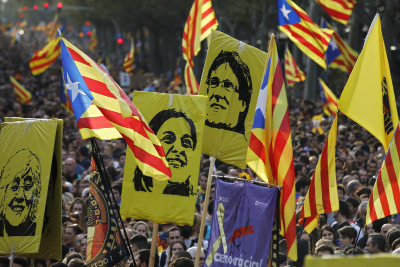 Protestors hold pictures of Catalan high-profile separatist politicians, Clara Ponsati, Anna Gabriel and Carles Puidgemont, from left to right, who are fugitives from Spanish law after fleeing the country, during a demonstration in Barcelona, Spain, Friday, Oct. 18, 2019.The Catalan regional capital is bracing for a fifth day of protests over the conviction of a dozen Catalan independence leaders. Five marches of tens of thousands from inland towns are converging in Barcelona's center for a mass protest. (AP Photo/Emilio Morenatti)