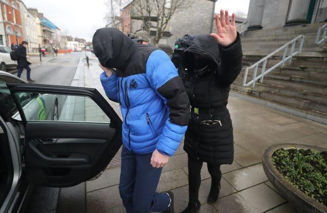 Patrick O'Brien (left) covers up as he leaves Tralee District Court where he escaped a criminal conviction (Niall Carson/PA)