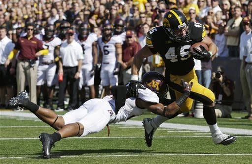 Iowa fullback Mark Weisman, right, breaks a tackle by Minnesota defensive back Cedric Thompson during an 8-yard touchdown run in the first half of an NCAA college football game, Saturday, Sept. 29, 2012, in Iowa City, Iowa. (AP Photo/Charlie Neibergall)