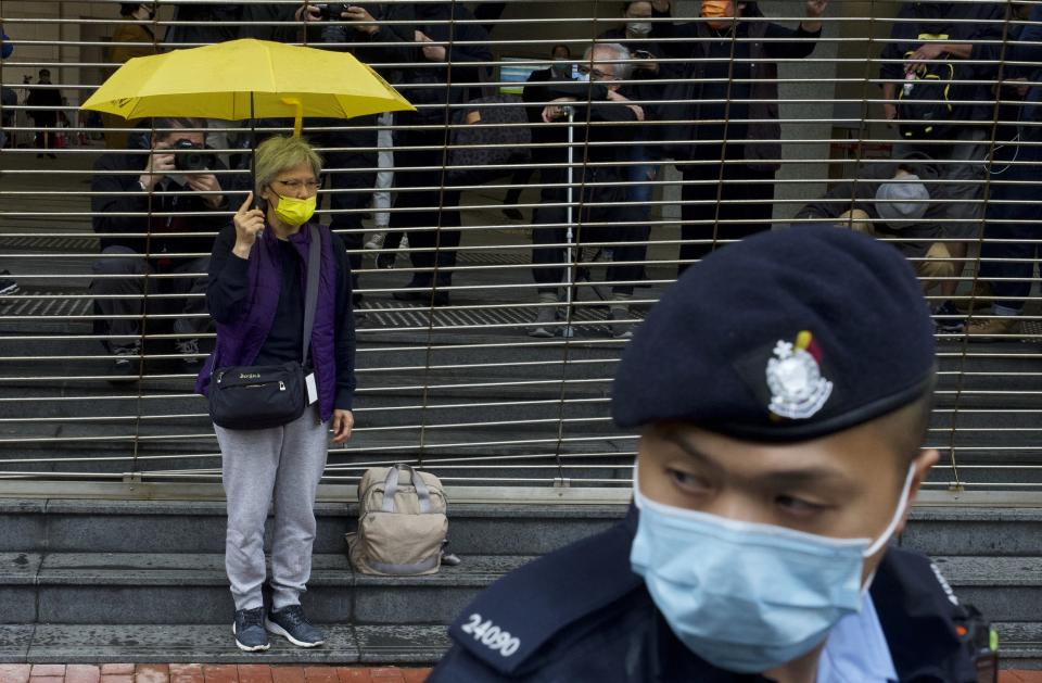 A pro-democracy supporter holding an umbrella queues up for a hearing outside a courthouse in Hong Kong, Thursday, March 4, 2021. A marathon court hearing for 47 pro-democracy activists in Hong Kong charged with conspiracy to commit subversion enters its fourth day on Thursday, as the court deliberates over whether the defendants will be granted bail. (AP Photo/Vincent Yu)