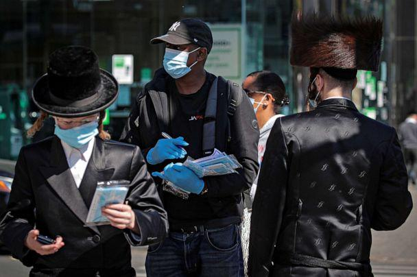 PHOTO:A member of New York City Test and Trace Corp. hands out masks to Ultra-Orthodox Jewish men in the Borough Park section of Brooklyn, where COVID-19 infection rates have gone up, in New York, Oct. 9, 2020. (Brendan Mcdermid/Reuters)
