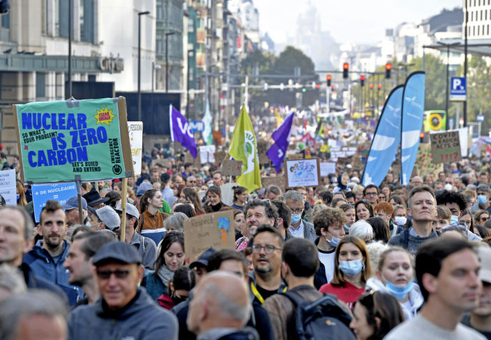 Protestors hold signs as they participate in a climate march and demonstration in Brussels, Sunday, Oct. 10, 2021. Some 80 organizations are joining in a climate march through Brussels to demand change and push politicians to effective action in Glasgow later this month.(AP Photo/Geert Vanden Wijngaert)