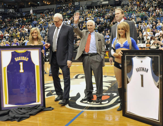 FILE - In this March 1, 2011, file photo, Los Angeles Lakers head coach Phil Jackson, center left, and Minnesota Timberwolves head coach Kurt Rambis, center right, stand alongside longtime Star Tribune of Minneapolis sports reporter and radio personality Sid Hartman, center, who waves to fans after he was honored prior to an NBA basketball game between the Timberwolves and the Los Angeles Lakers in Minneapolis. Hartman, who turned 100 on Sunday, March 15, 2020, served as the acting general manager of the Minneapolis Lakers who later became the Los Angeles Lakers. (AP Photo/Jim Mone, File)