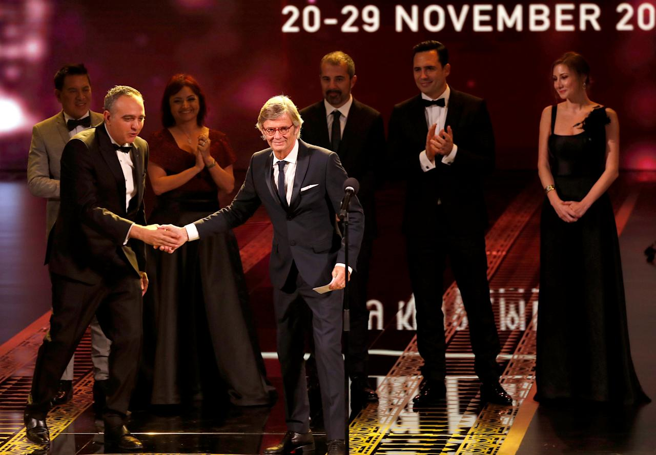 Bille August (C) Danish director and chairman of the jury shakes hand with Mohamed Hefzy, president of the 40th edition of the Cairo International Film Festival during the opening ceremony at the Opera House in Cairo, Egypt November 20, 2018. Picture taken November 20, 2018. REUTERS/Amr Abdallah Dalsh