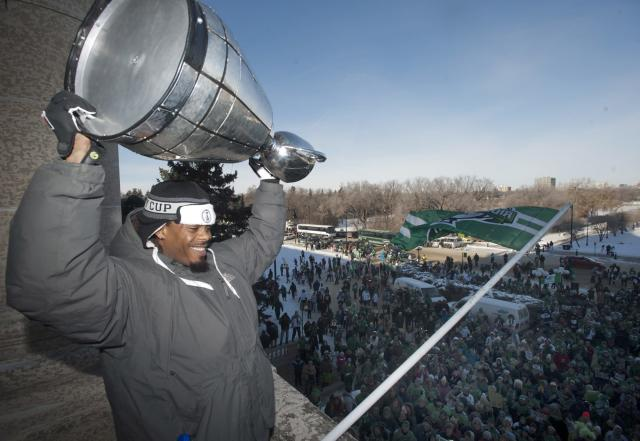 Saskatchewan Roughriders defensive back Dwight Anderson lifts the Grey Cup to fans as he stands on a balcony at the Saskatchewan Legislative building after the Grey Cup parade on Tuesday, Nov. 26, 2013 in Regina, Saskatchewan. Thewan Roughriders defeated the Hamilton Tiger-Cats 45-23 in the 101st CFL Grey Cup on Sunday. (AP Photo/The Canadian Press, Liam)