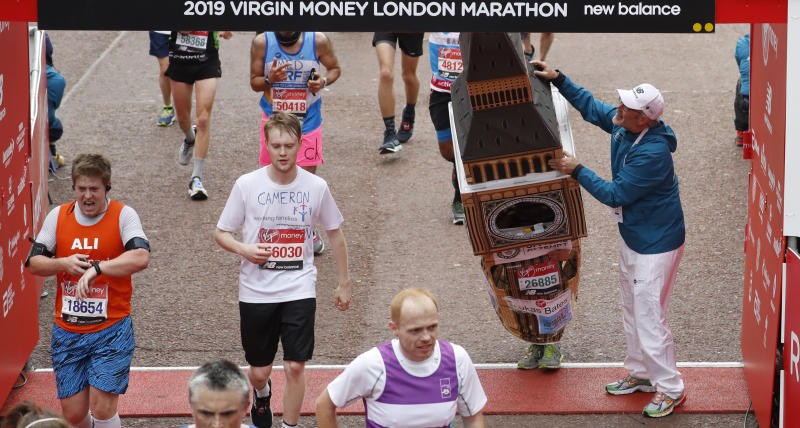 Lukas Bates wearing a costume of the Queen Elizabeth Tower (known as Big Ben) is helped by an official as he attempts to get past the finishing line, during the 39th London Marathon in London, Sunday, April 28, 2019. (AP Photo/Alastair Grant)