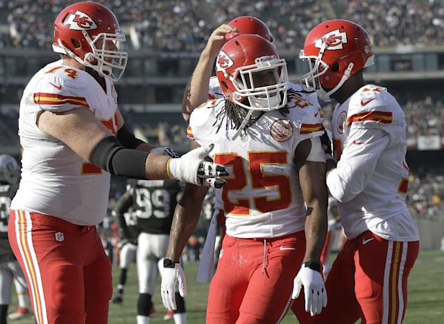 Kansas City Chiefs running back Jamaal Charles (25) celebrates after scoring on a 39-yard touchdown reception with guard Geoff Schwartz, left, quarterback Alex Smith, rear, and wide receiver Donnie Avery against the Oakland Raiders during the first quarter of an NFL football game in Oakland, Calif., Sunday, Dec. 15, 2013. (AP Photo/Marcio Jose Sanchez)