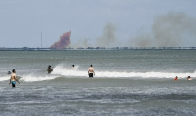 A cloud of orange smoke rises over Cape Canaveral