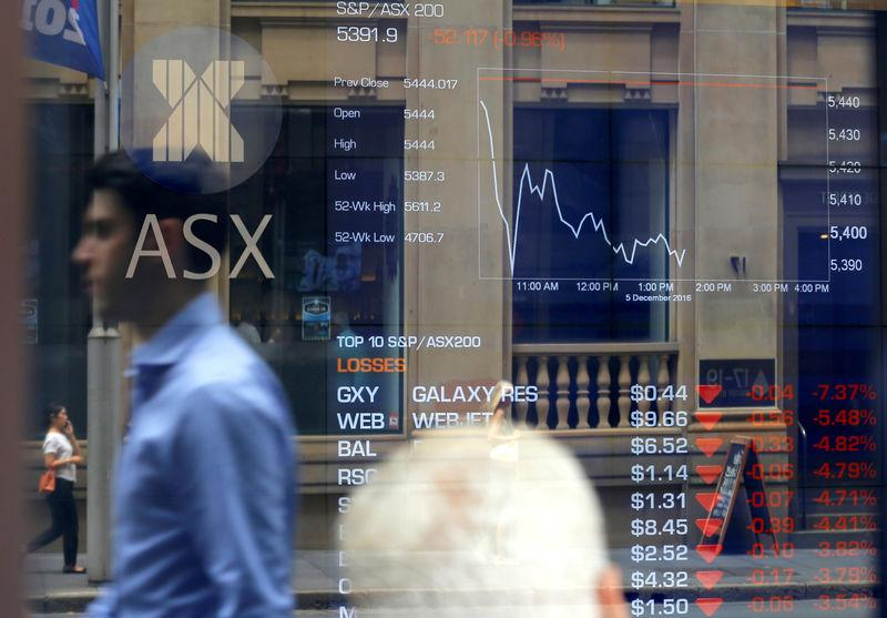 Pedestrians are reflected on a window as they walk past an investor looking at a board displaying stock prices at the Australian Securities Exchange in Sydney, Australia