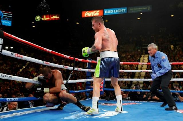 Canelo Alvarez, centre, knocks out Sergey Kovalev in the 11th round of their WBO light heavyweight fight in Las Vegas, Nevada (AFP Photo/Steve Marcus)