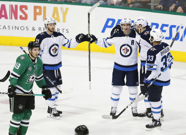 Winnipeg Jets forward Mark Scheifele (55) is congratulated by teammates after scoring a goal during the second period of an NHL hockey game against the Dallas Stars, Saturday, Feb. 24, 2018, in Dallas. (AP Photo/Brandon Wade)