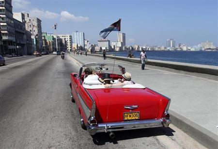 Tourists ride a U.S.-made 1957 Chevrolet Bel-Air convertible car on Havana's seafront boulevard 'El Malecon'