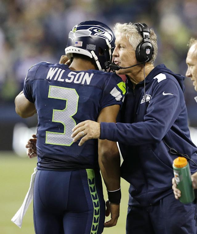 Seattle Seahawks head coach Pete Carroll, right, embraces quarterback Russell Wilson late in the NFL football game against the San Francisco 49ers, Sunday, Sept. 15, 2013, in Seattle. The Seahawks beat the 49ers 29-3. (AP Photo/Elaine Thompson)