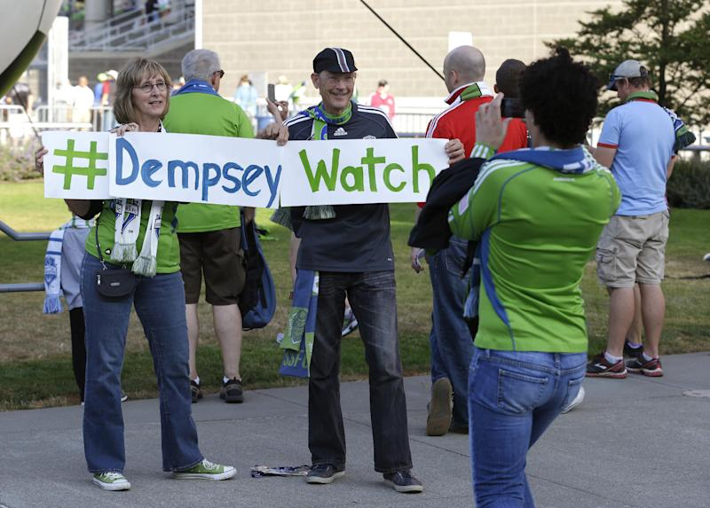 Seattle Sounders fans Larry McCann, right, and Nancy Cooper, left, both of Seattle, display a sign that has the Twitter hashtag #DempseyWatch outside CenturyLink Field before a MLS soccer match between the Sounders and FC Dallas. Clint Dempsey, captain of the United States Men's National Team, who previously played for Tottenham Hotspur in the English Premier League, has been linked by reports to joining the Seattle Sounders. (AP Photo/Ted S. Warren)