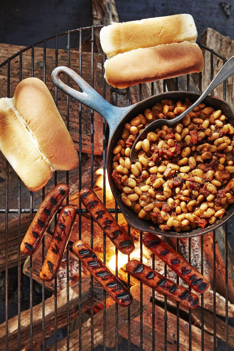 """<p>Quick cooking classic baked beans pair perfectly with grilled hot dogs and buns. This is basically summer on a grill!</p><p><strong><a href=""""https://www.countryliving.com/food-drinks/a28189870/hot-dogs-with-quick-cast-iron-beans-recipe/"""" rel=""""nofollow noopener"""" target=""""_blank"""" data-ylk=""""slk:Get the recipe"""" class=""""link rapid-noclick-resp"""">Get the recipe</a>.</strong><br></p>"""