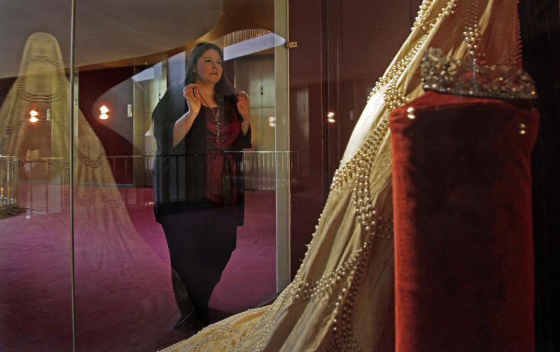 "Soprano Angela Meade presses against a class display to view the 1921 Elvira costume from the first performance of Giuseppi Verdi's opera ""Ernani,"" on Wednesday, Feb. 15, 2012 at the Lincoln Center in New York. Meade will reach an international audience in a single performance as she plays the lead female role, Elvira, in the Metropolitan Opera's high-definition global broadcast performance of ""Ernani"" on Saturday, Feb. 25. (AP Photo/Bebeto Matthews)"
