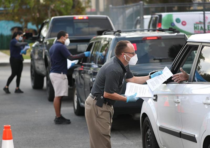City of Hialeah employees hand out unemployment applications to people in Florida