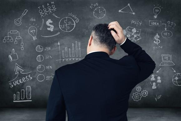 A man in a suit scratches his head while staring at a chalkboard covered by diagrams.