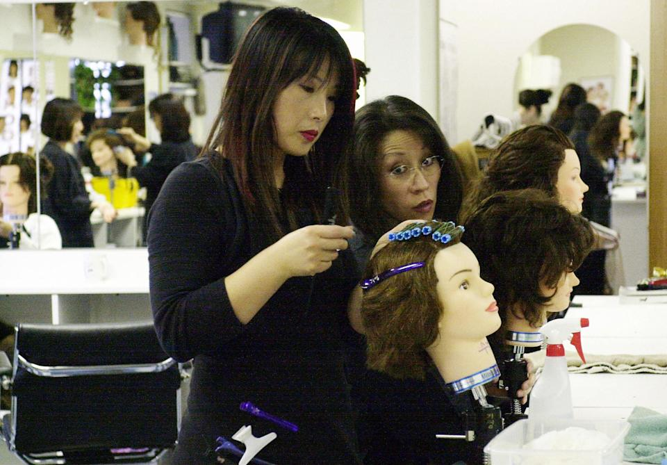 Cosmopolitian Beauty and Barber School students practice cutting hair at their clinic on March 19, 2004, in Annandale, Virginia. (AFP PHOTO/Joyce NALTCHAYAN)
