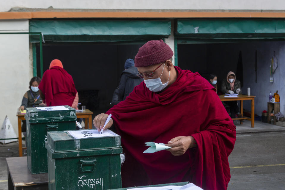 An exile Tibetan Buddhist monk wearing a mask as a precaution against the coronavirus casts his ballot in Dharmsala, India, Sunday, Jan. 3, 2021. Exile Tibetans Sunday voted in the first round to elect a new political leader and members of the Tibetan parliament in exile. (AP Photo/Ashwini Bhatia)