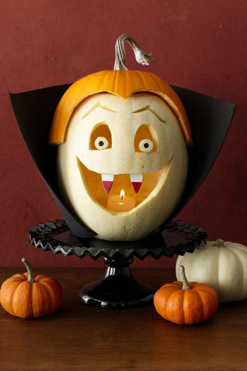 """<p>To make this blood-sucker, carve eyes, brows, and a mouth into a hollowed-out white pumpkin. Make pupils with a permanent marker. Paint <span class=""""redactor-unlink"""">large wood teardrops</span> white with red tips to make fangs; push into place. Top with a widow's peak cut from a slightly larger orange pumpkin. Pin a <span class=""""redactor-unlink"""">black craft foam</span> collar around the pumpkin. </p>"""