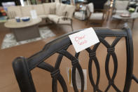 In this July 6, 2021, photo a sign is seen on a sold patio furniture floor model at Valley View Farms in Cockeysville, Md. People used to go to Valley View Farms to buy five tomato plants and end up with $5,000 in patio furniture. But this year is different. After a record burst of sales in March, the showroom floor is almost empty of outdoor chairs, tables and chaises for people to buy. The garden supply store in suburban Baltimore has been waiting six months for a shipping container from Vietnam. It's full of $100,000 worth of wicker and aluminum furniture. Half of the container has already been sold by showing customers photographs. The container should have arrived in February, but it reached U.S. waters on June 3 and has yet to dock in Long Beach, Calif.(AP Photo/Julio Cortez)