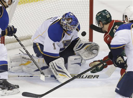 St. Louis Blues goalie Brian Elliott (1) stops a shot as Minnesota Wild's Cal Clutterbuck (22) looks for a rebound in the first period of an NHL hockey game on Thursday, April 11, 2013 in St. Paul. (AP Photo/Jim Mone)