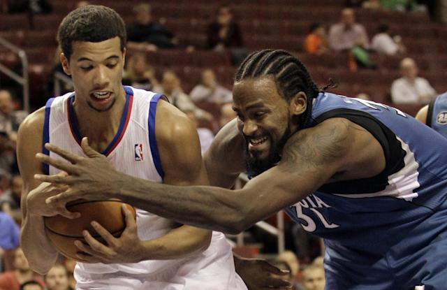 Minnesota Timberwolves' Ronny Turiaf, right, and Philadelphia 76ers' Michael Carter-Williams fight for the ball in the first half of a preseason NBA basketball game, Wednesday, Oct. 23, 2013, in Philadelphia. (AP Photo/Laurence Kesterson)