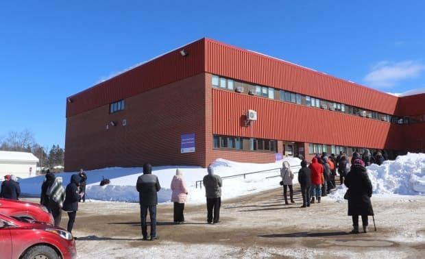 People wait in line outside Dr. Losier Middle School in Miramichi on Thursday for a COVID-19 mass testing clinic.