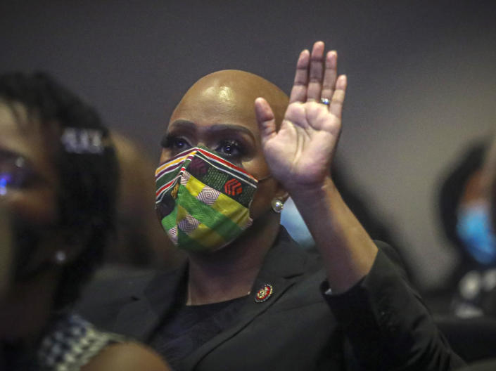 U.S. Rep. Ayanna Pressley of Massachusetts raises her hand during a memorial service for George Floyd at North Central University, on Thursday, June 4, 2020, in Minneapolis. Hollywood celebrities, musicians and political leaders gathered in front of the golden casket of George Floyd whose death at the hands of police sparked global protests. (AP Photo/Bebeto Matthews)