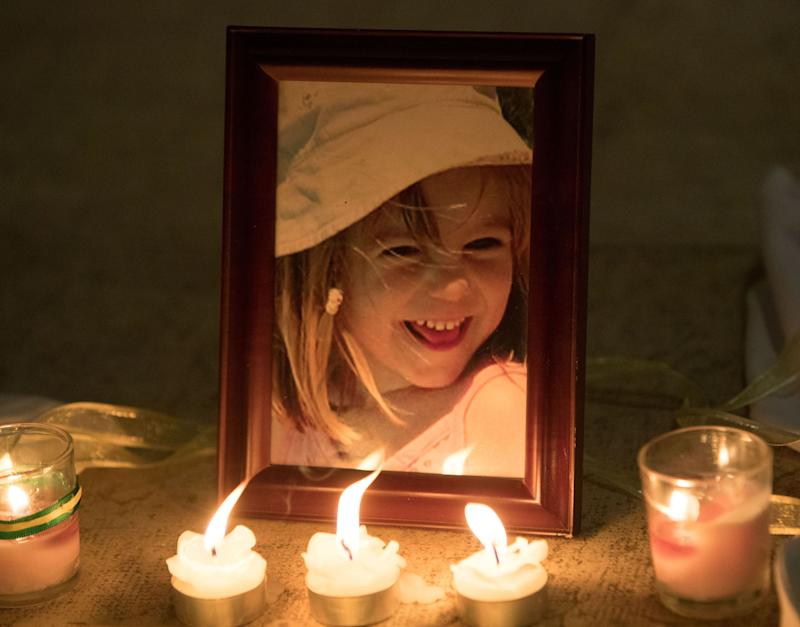 Candles are placed next to a photo of Madeleine McCann at a church in Praia Da Luz, Portugal (Picture: PA)