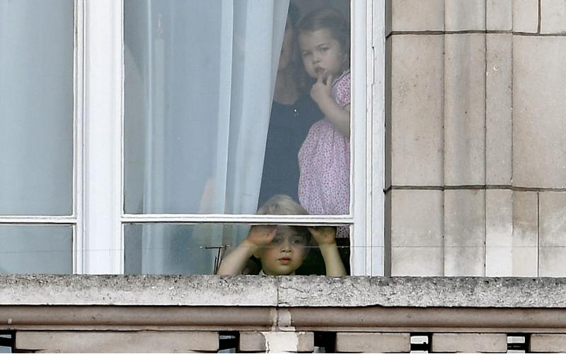Prince George and Princess Charlotte of Cambridge watch through the window of Buckingham Palace as they attend Trooping the Colour at Buckingham Palace - Credit: Andrew Parsons