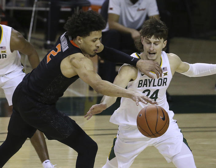 Oklahoma State guard Cade Cunningham (2) has the ball striped by Baylor guard Matthew Mayer (24) in the second half of an NCAA college basketball game, Thursday, March 4, 2021, in Waco, Texas. (AP Photo/Jerry Larson)