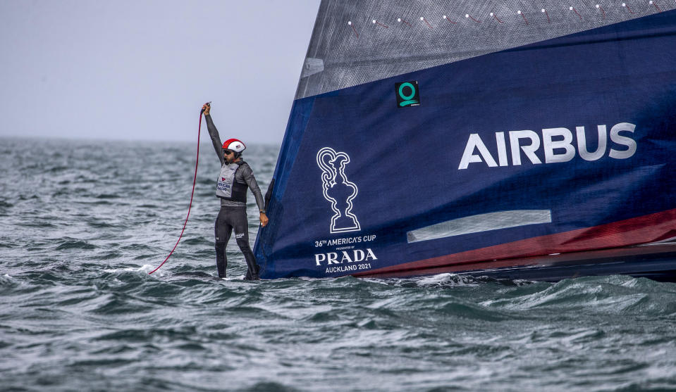 A crewman from United States' American Magic boat Patriot signals for assistant after it capsized during its race against Italy's Luna Rossa on the third day of racing of the America's Cup challenger series on Auckland's Waitemate Harbour, New Zealand, Sunday, Jan. 17, 2021. (Michael Craig/NZ Herald via AP)